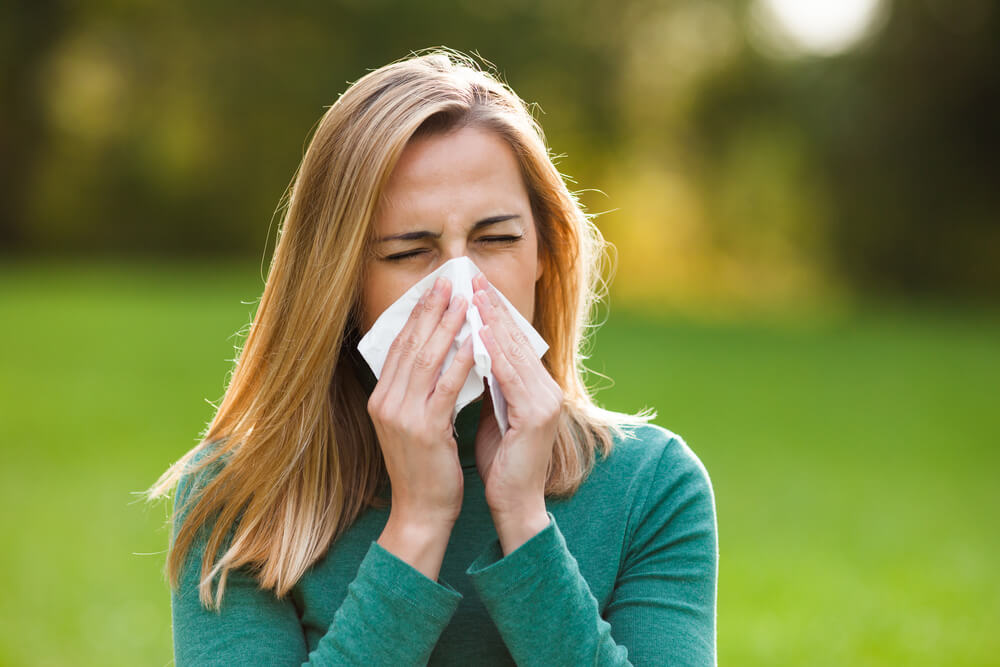 A young woman is suffering from a runny nose, one of the most common signs of seasonal allergies