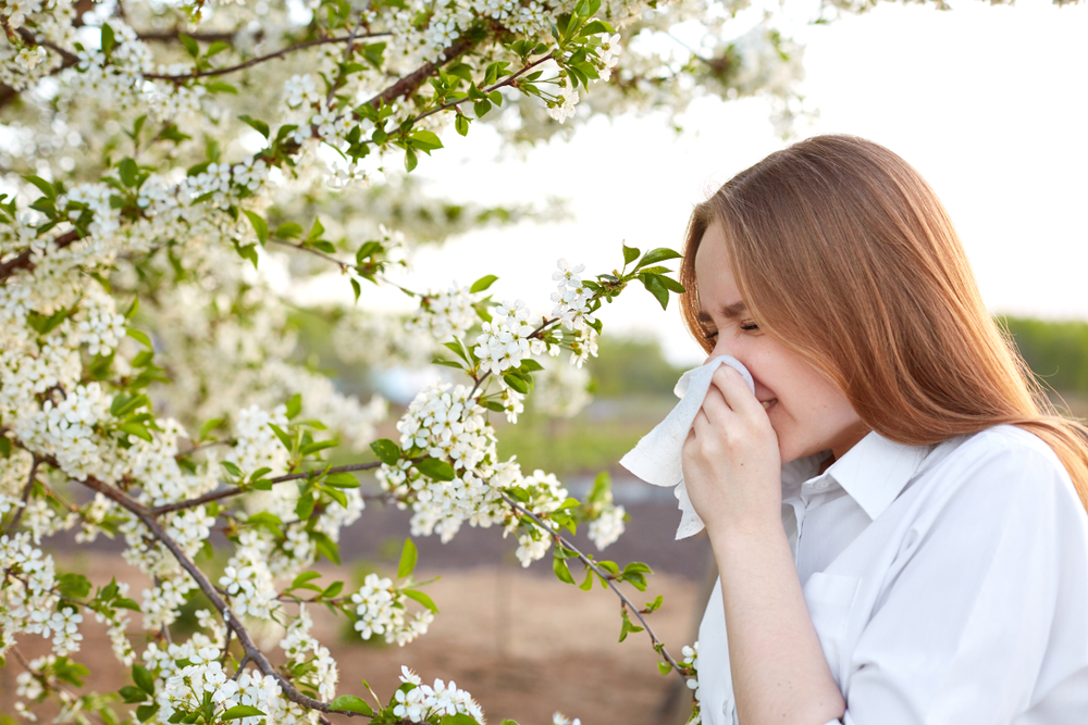 A woman suffering from allergy is standing near a blooming tree