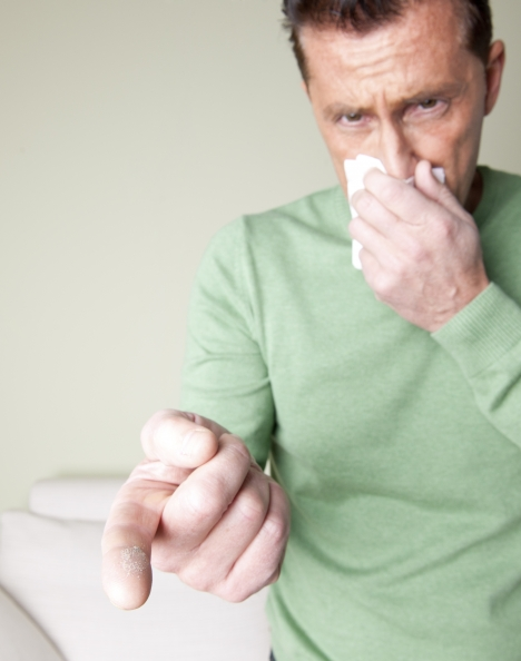 A man is sneezing because he is allergic to dust